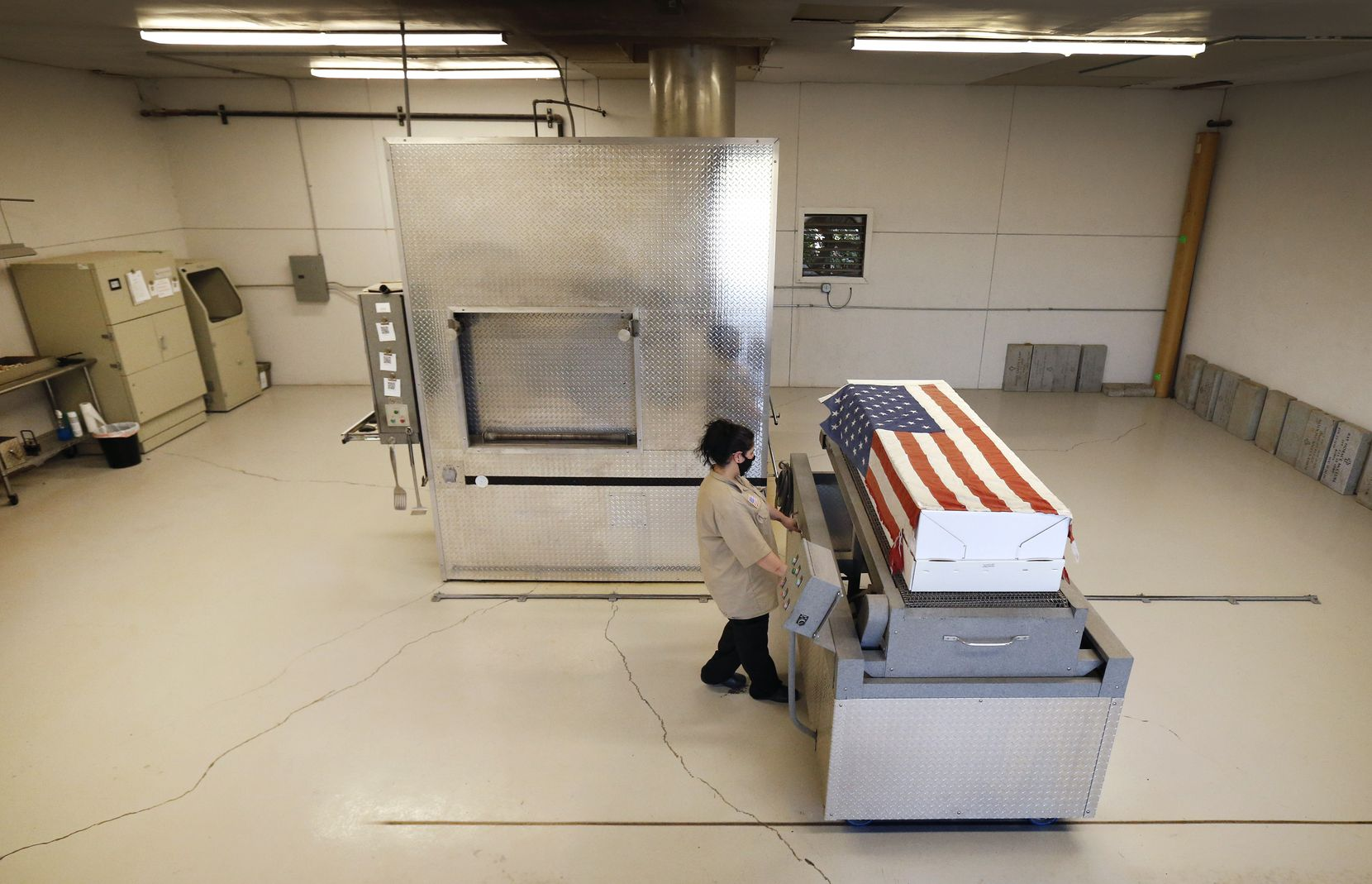 Loni Varela moves a container bearing a Navy veteran to a chamber for cremation at Simple Cremations in Fort Worth. Varela played taps on a Bluetooth during the ceremony. Retired flags are used for such ceremonies, with a star cut out and given to the family.