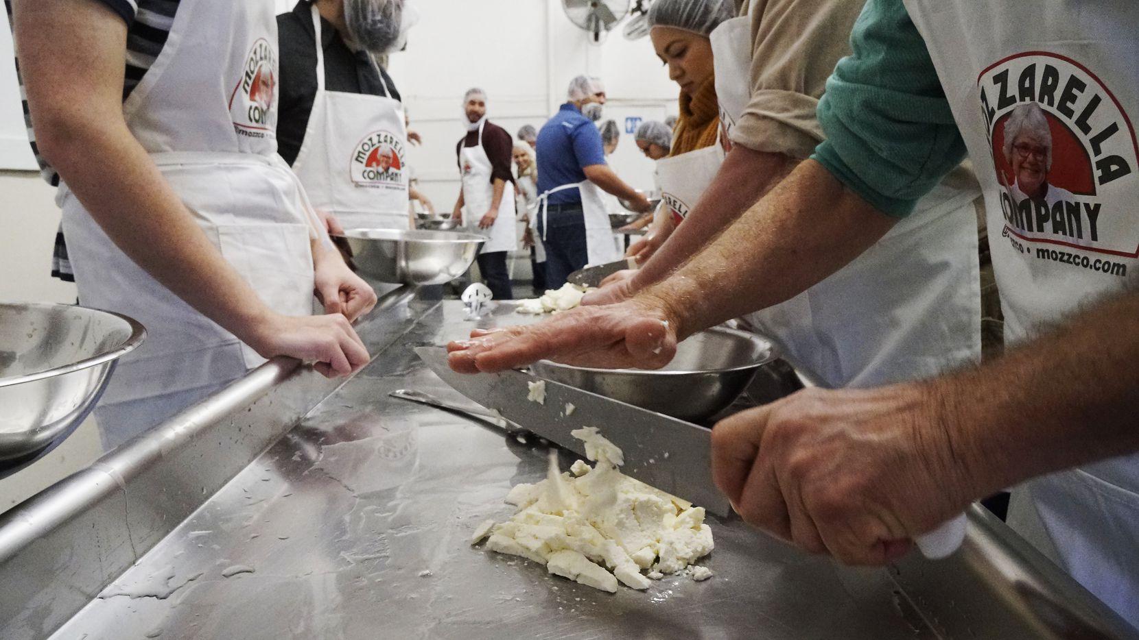 Student prepare to make cheese during a class at the Mozzarella Company.