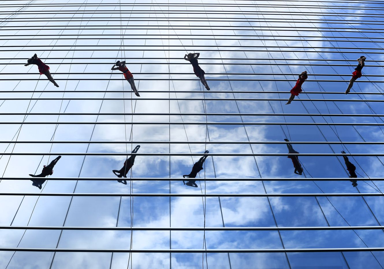 Members of the Bandaloop vertical dance company perform on the side of the KPMG building during the groundbreaking ceremony.