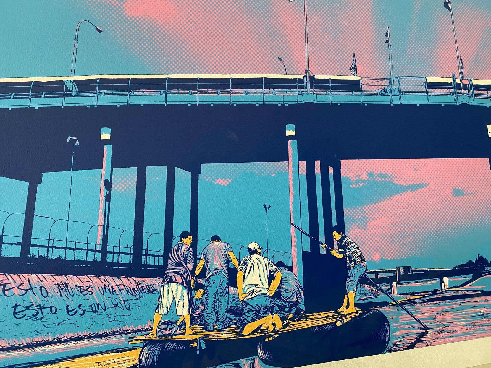 """El Paso muralist Jesus Alvarado, El Cimi, painted this screen print in 2015 to depict life along the border witht the Santa Fe International Bridge in the background. The caption in Spanish reads: """"This is not a border. This is just a river."""""""