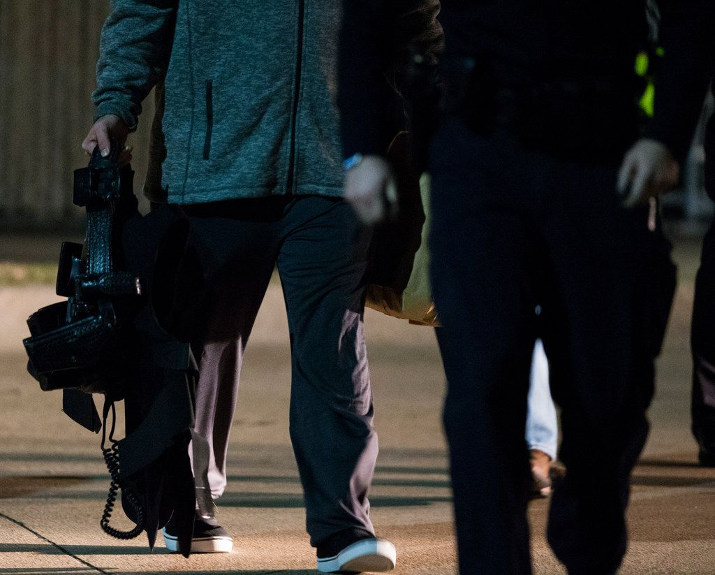A police gun belt is carried as people leave the emergency room at Medical City Plano hospital in Plano, Texas after a Richardson, Texas police officer was shot and killed on Wednesday, February 7, 2018, at an apartment complex in Richardson.
