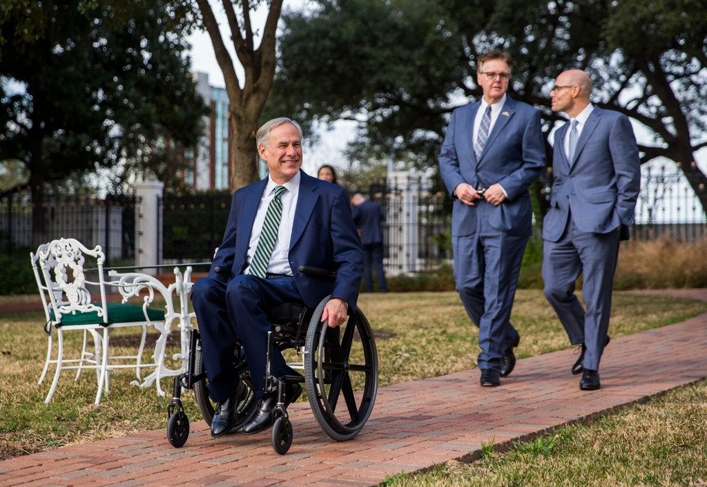 Governor Greg Abbott, Lt. Governor Dan Patrick and Speaker of the House Dennis Bonnen watch as the governor's dogs, Peaches and Pancake, play in the yard after a press conference at the Governor's mansion on the second day of the 86th Texas legislature on Wednesday, January 9, 2019 in Austin, Texas.