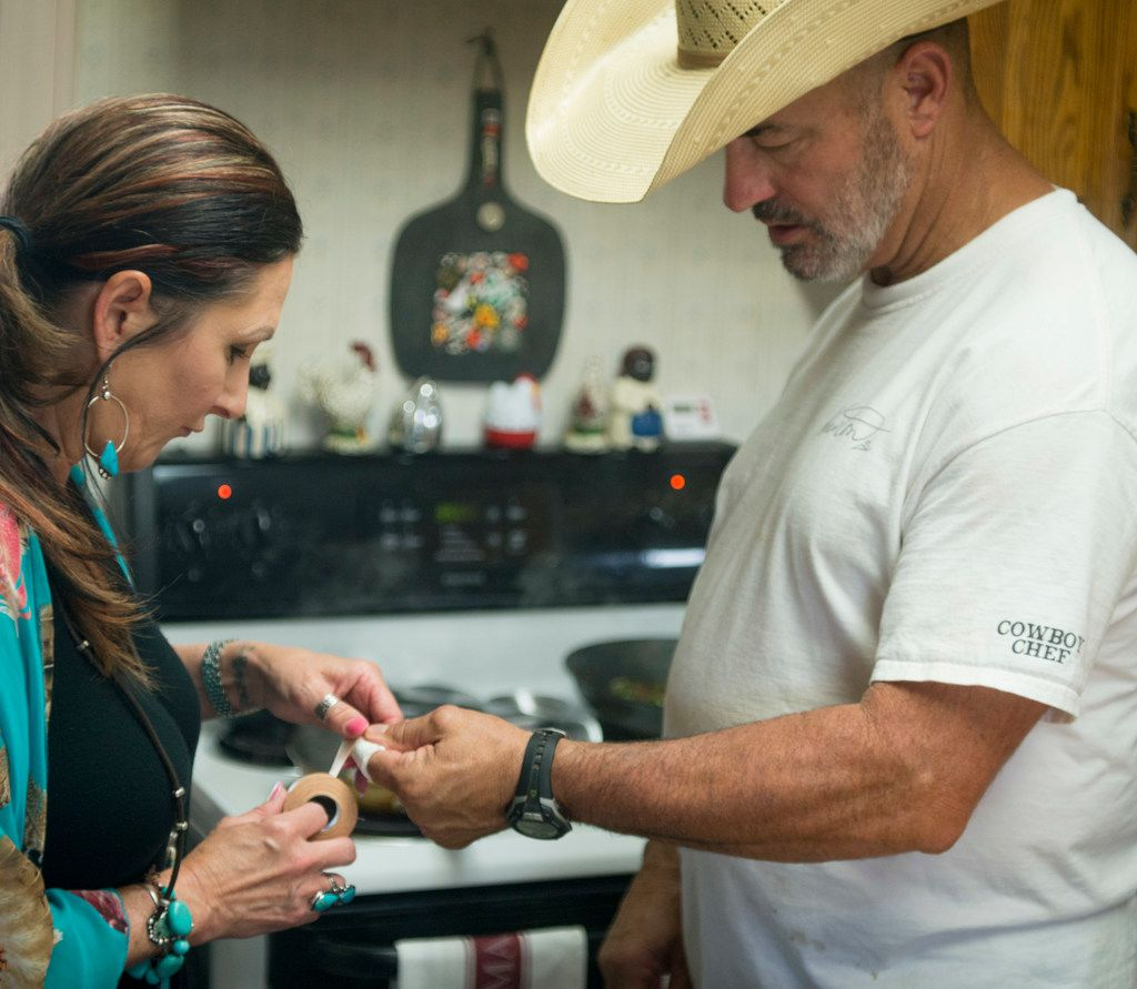 Mike Newton, known as the Cowboy Chef, gets an assist with a cut finger from his wife Melanie at their ranch home in Lipan, Texas on July 17, 2018. (Robert W. Hart/Special Contributor)