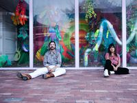"Tyler Germaine and Mariell Guzman, the duo behind the art collective Denim Disco, sit outside of their art installation ""Synthetic Aesthetic,"" which resides inside a converted shipping container gallery space in Fort Worth."