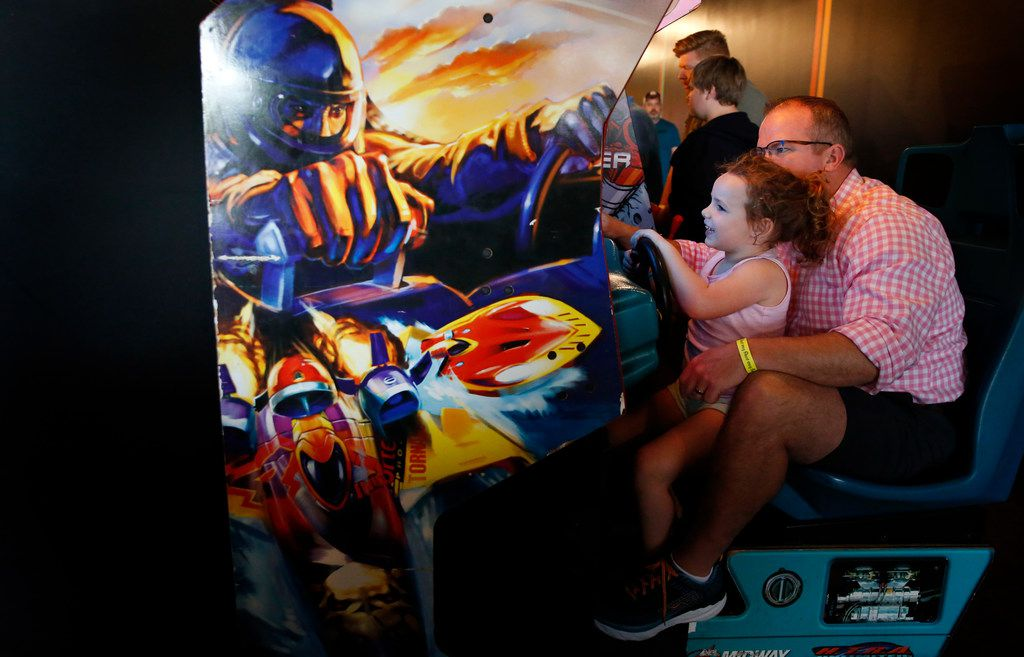 James Purl helps his daughter Collins Purl, 5, play a racing game at Free Play in Richardson.