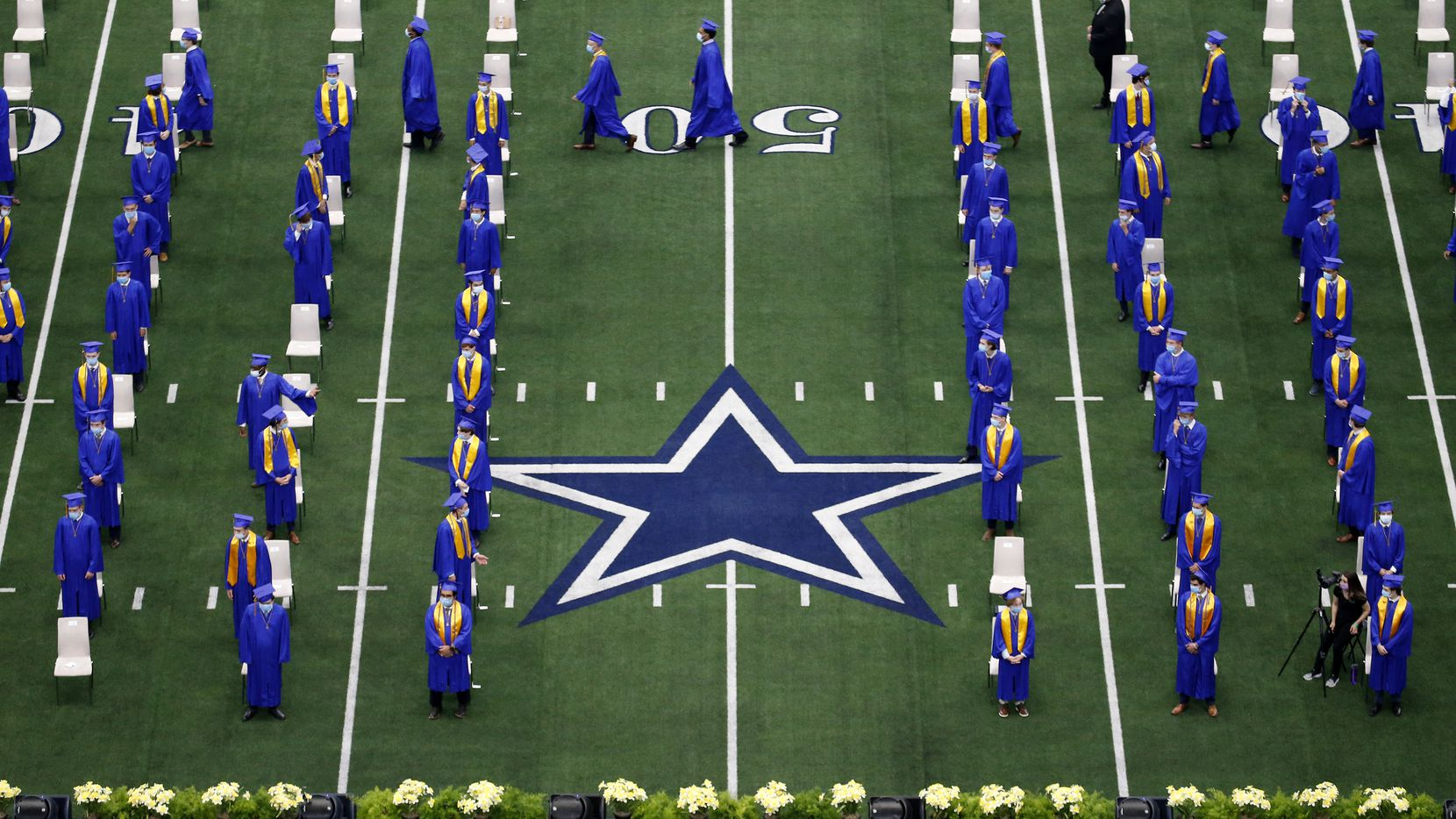 Graduates from the Jesuit College Preparatory School of Dallas file into their socially-distanced seats for commencement last year in this file photo. Currently, all 10 Frisco ISD high schools are scheduled to have an in-person graduation this year at the Ford Center at The Star.