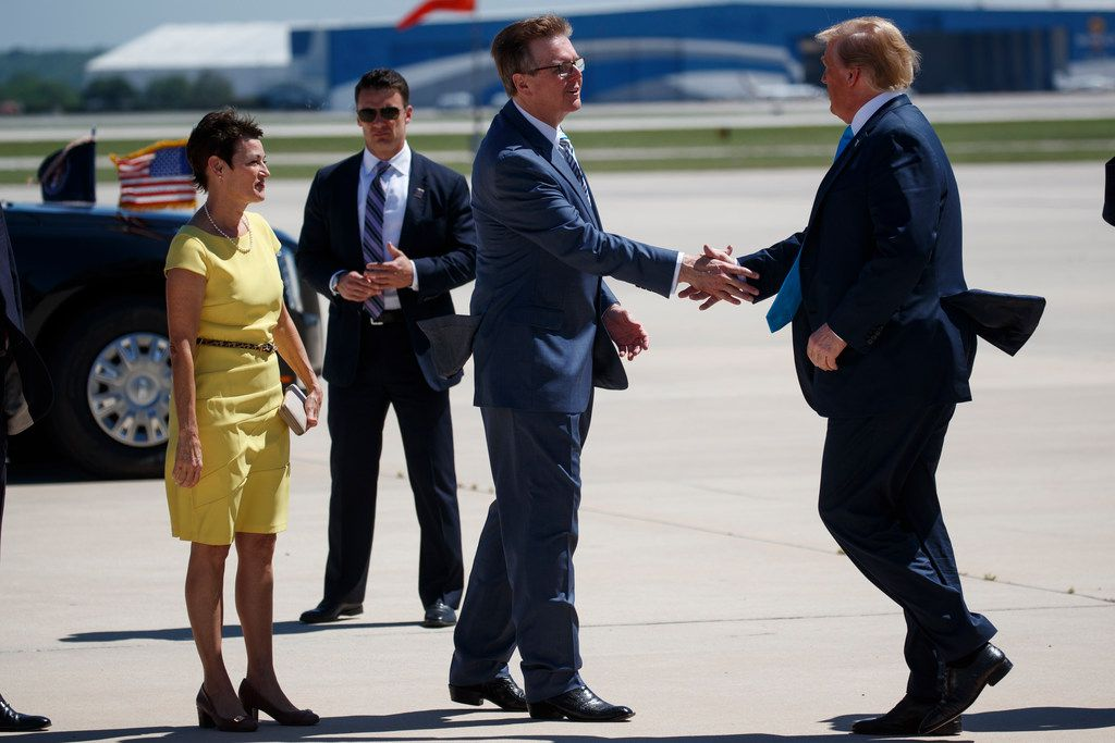 Texas State Senator Donna Campbell, left, watches as Lt. Gov. Dan Patrick, R-Texas, greets President Donald Trump as he arrives at San Antonio International Airport on April 10, 2019.