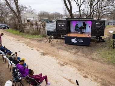 Shaun Martin performs outside of Marsha Jackson's home in Dallas on Friday, Feb. 26, 2021. Quincy Roberts, the contractor who moved Shingle Mountain, surprised Jackson with the concert. (Juan Figueroa/ The Dallas Morning News)