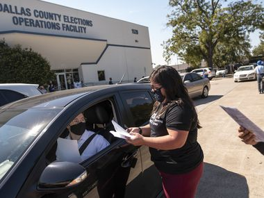 Laura Varela, bilingual program coordinator for Dallas County Elections, helps Alex Ballard, 23, to register to vote in Dallas County, outside of the Dallas County Elections Operations Facility in Dallas, Oct. 5, 2020.