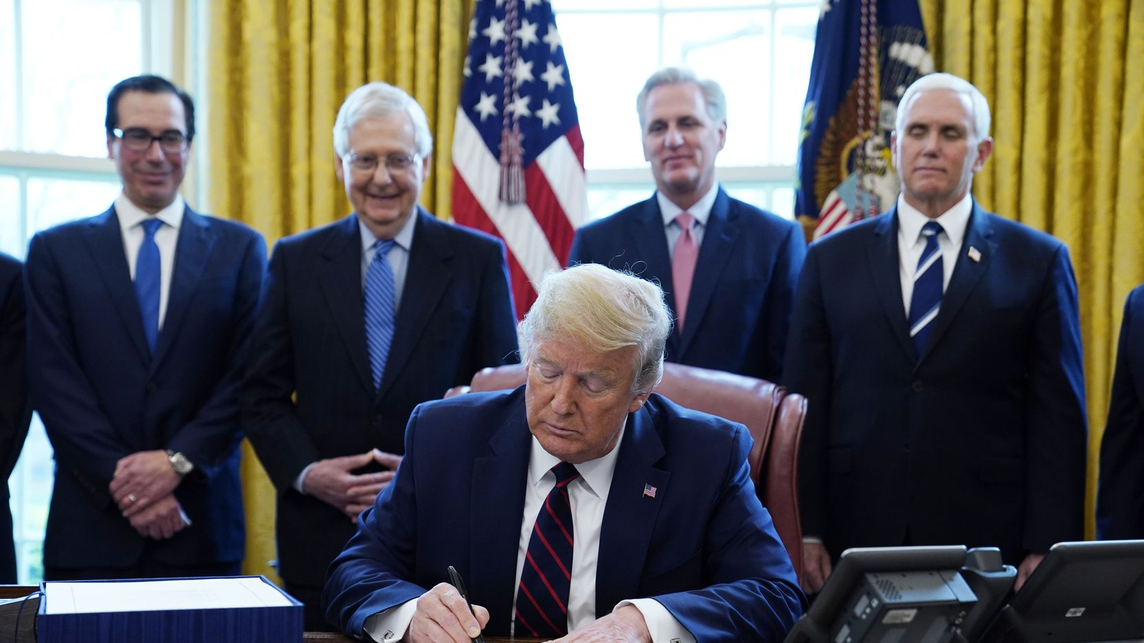 President Donald Trump signs the coronavirus stimulus relief package as from left, Treasury Secretary Steven Mnuchin, Senate Majority Leader Mitch McConnell of Ky., House Minority Kevin McCarthy of Calif., and Vice President Mike Pence, look on. Direct deposited stimulus payments began this week.