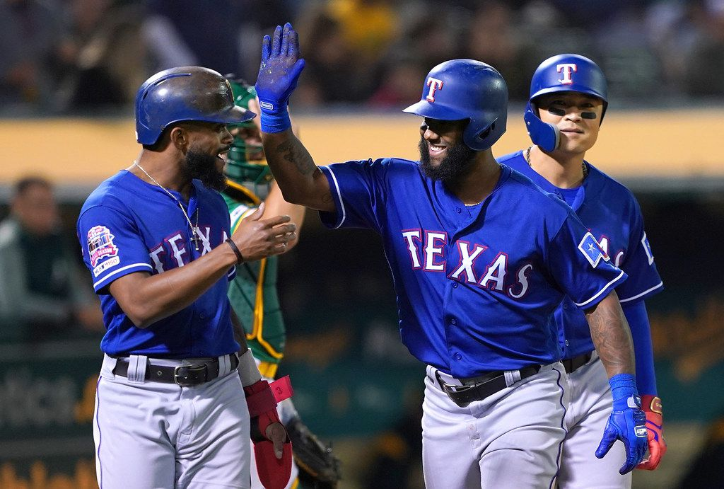 OAKLAND, CA - JULY 25:  Danny Santana #38 of the Texas Rangers is congratulated by Shin-Soo Choo #17 and Delino DeShields #3 after Santana hit a grand slam home run against the Oakland Athletics in the top of the six inning at Ring Central Coliseum on July 25, 2019 in Oakland, California.  (Photo by Thearon W. Henderson/Getty Images)