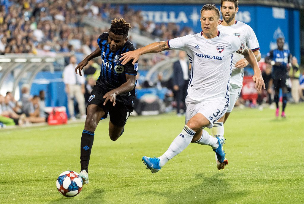 Montreal Impact's Orji Okwonkwo, left, challenges FC Dallas' Reto Ziegler during second-half MLS soccer match action in Montreal, Saturday, Aug. 17, 2019. (Graham Hughes/The Canadian Press via AP)