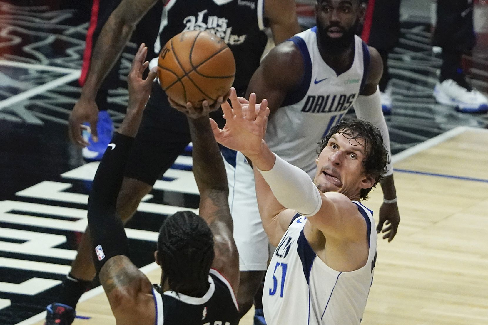 Dallas Mavericks center Boban Marjanovic (51) defends against LA Clippers guard Paul George (13) during the first quarter of an NBA playoff basketball game at the Staples Center on Wednesday, June 2, 2021, in Los Angeles.  (Smiley N. Pool/The Dallas Morning News)