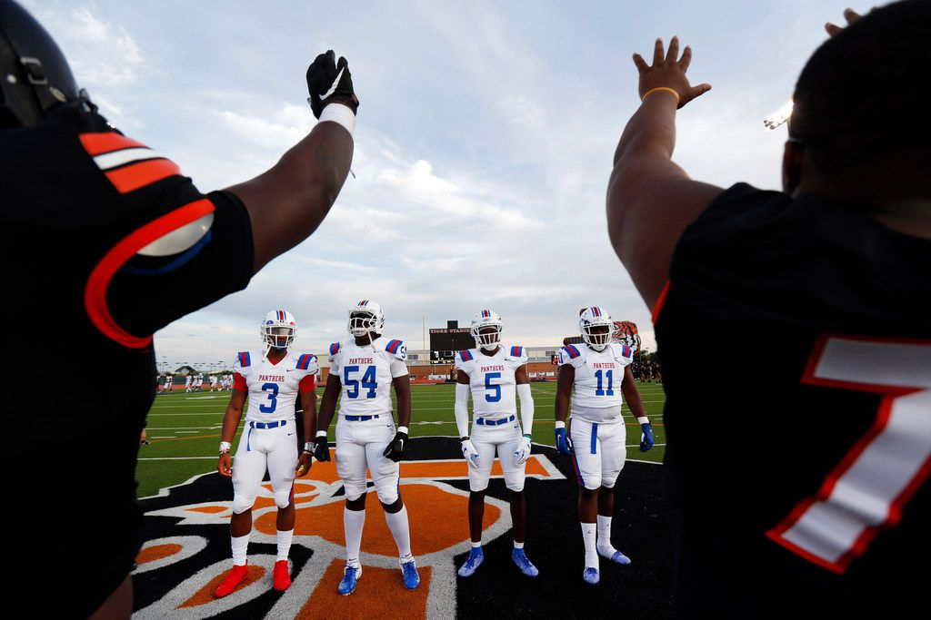 Lancaster team captains raise the hands as their team is introduced.  Duncanville team captains Ja'Quinden Jackson (3), Savion Byrd (54), Christopher Thompson (5) and James Mitchell (11) line up during the coin toss before their season opening game at Beverly D. Humphrey Tiger Stadium in Lancaster Texas, Friday, August 30, 2019. (Tom Fox/The Dallas Morning News)