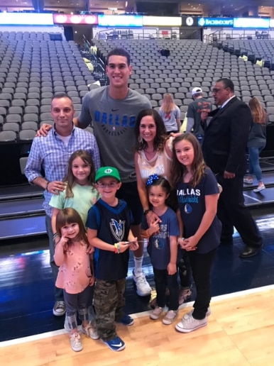 Dwight Powell poses after the home opener Saturday with the family of a cancer patient at UT Southwestern. Powell, coach Rick Carlisle and other Mavericks met with about 120 cancer patients who attended the game after the Mavericks' 140-136 win over Minnesota.
