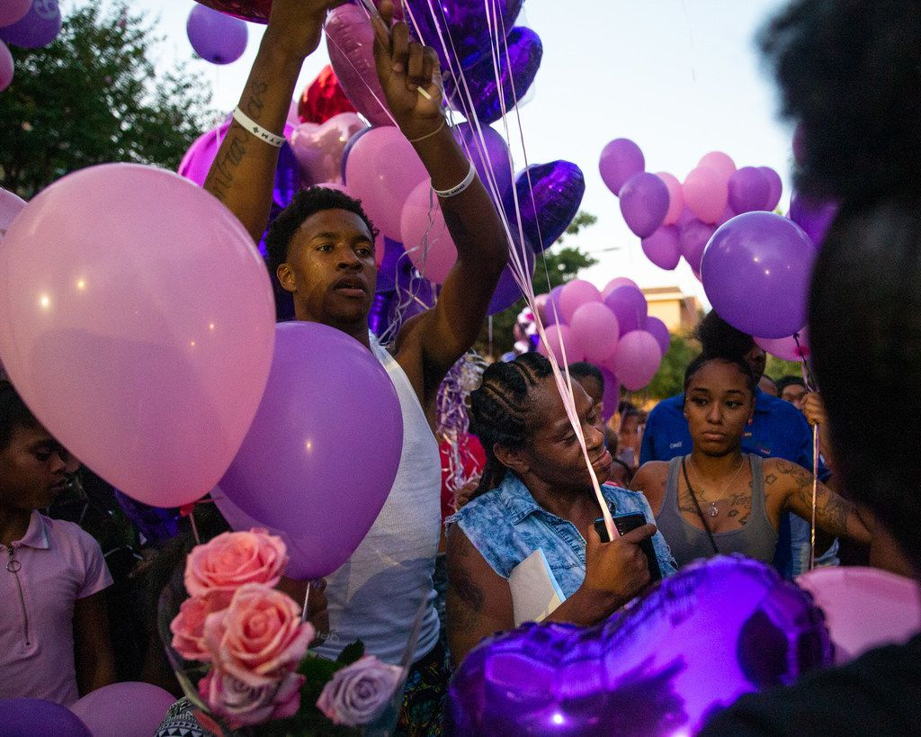 Tonya Elder (center) and other mourners gather to honor the life of Elder's 9-year-old granddaughter, Brandoniya Bennett, during a vigil at the Roseland Townhomes.