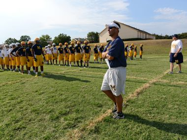 Jeff Smith, McKinney High School head football coach, head football coach, instructs players during an afternoon practice. The coaches have implemented a character curriculum for their football players.