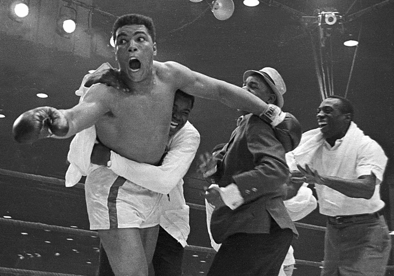 Cassius Clay's handlers hold him back as he reacts after he is announced the new heavyweight champion of the world on a seventh round TKO against Sonny Liston in Miami Beach, Fla., on Feb. 25, 1964, yelling to the ringside reporters 'eat your words'.