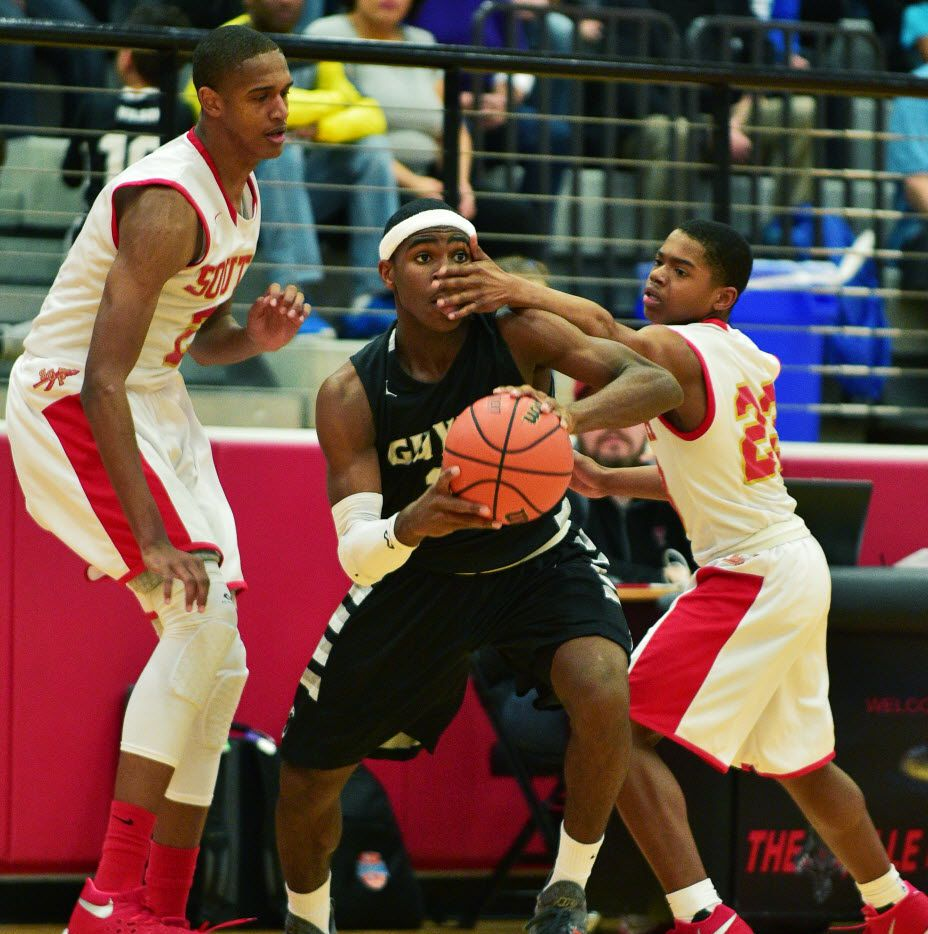 Guyer freshman guard Devion Harmon (11) get a hand to the face while covered by South Grand Prarie senior forward Harrison Henderson (2) and freshman guard Bryce Cook (23), Friday, February 26, 2016, at Colleyville Heritage High School in Colleyville, Texas. David Minton/DRC ORG XMIT: txder