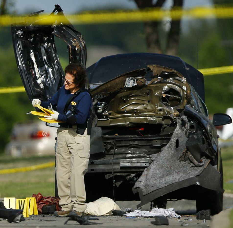 A FBI Evidence Response team member picks up yellow markers after collecting evidence near the damaged car at the crime scene.