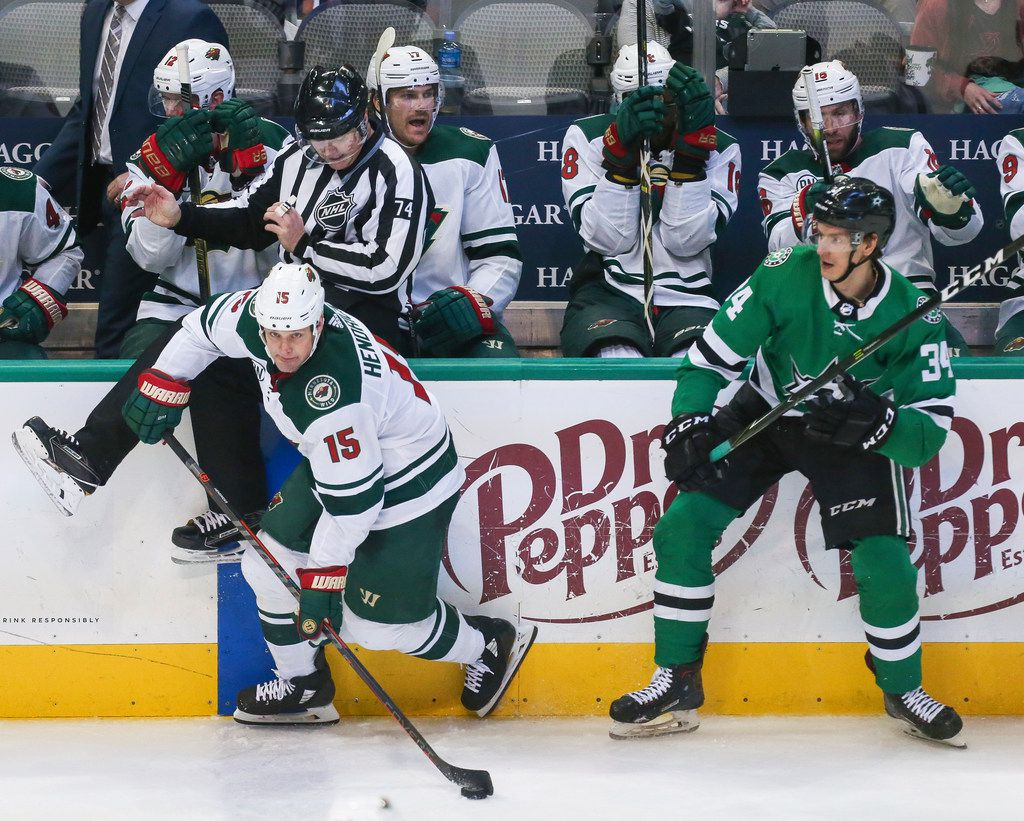 Minnesota Wild center Matt Hendricks (15) breaks past Dallas Stars right wing Denis Gurianov (34) and linesman Lonnie Cameron (74) during the third period of a match between the Dallas Stars and the Minnesota Wild on Friday, Feb. 1, 2019 at the American Airlines Center in Dallas. (Ryan Michalesko/The Dallas Morning News)