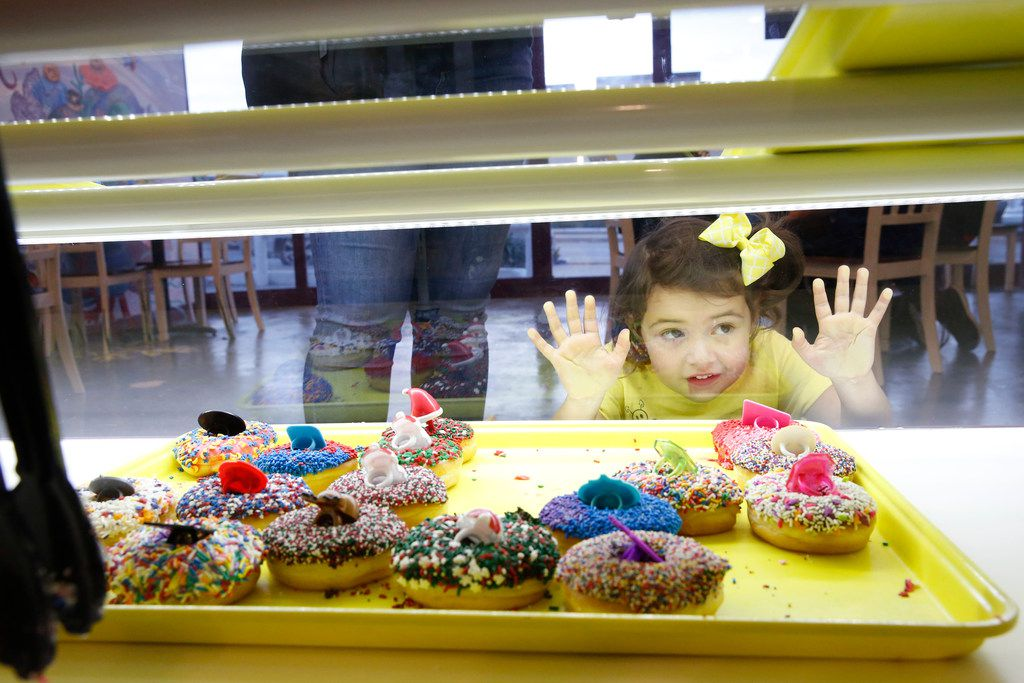 Gwendolyn Trujillo, 3, eyes the doughnuts before making a selection at the new Jarams Donuts in Lakewood Dallas.