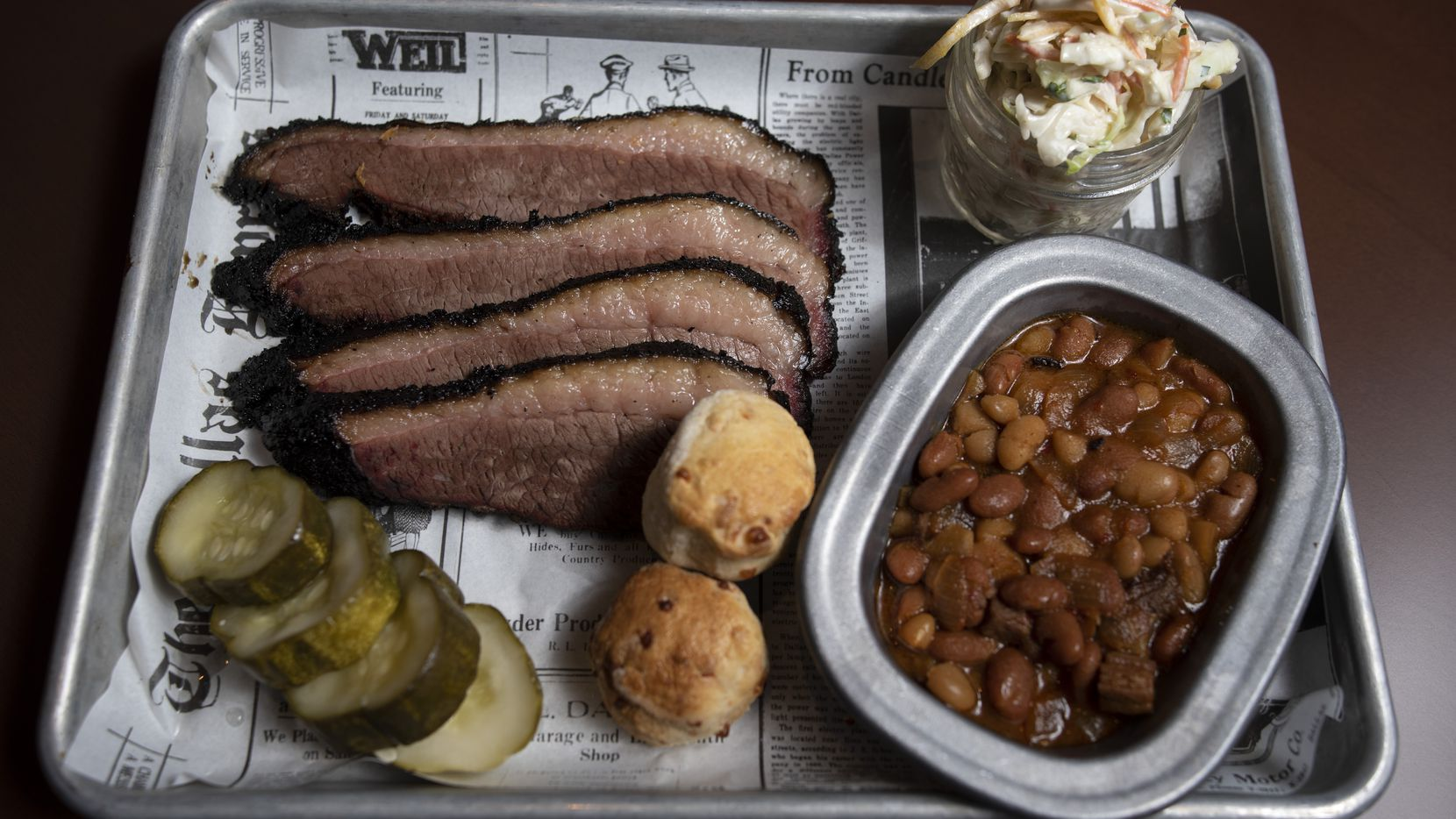 The menu at Seely's Mill, a barbecue restaurant in the new Beeman Hotel in Dallas, includes sliced brisket, burnt ends pit beans, slaw and cheddar biscuits. The restaurant opened Sept. 25, 2020.
