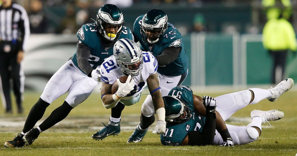 Dallas Cowboys running back Ezekiel Elliott (21) leaps for yards as he is tackled by Philadelphia Eagles free safety Rodney McLeod (23), Philadelphia Eagles defensive end Vinny Curry (75) and Philadelphia Eagles defensive tackle Fletcher Cox (91) during the second half of play at Lincoln Financial Field in Philadelphia on Sunday, December 22, 2019.