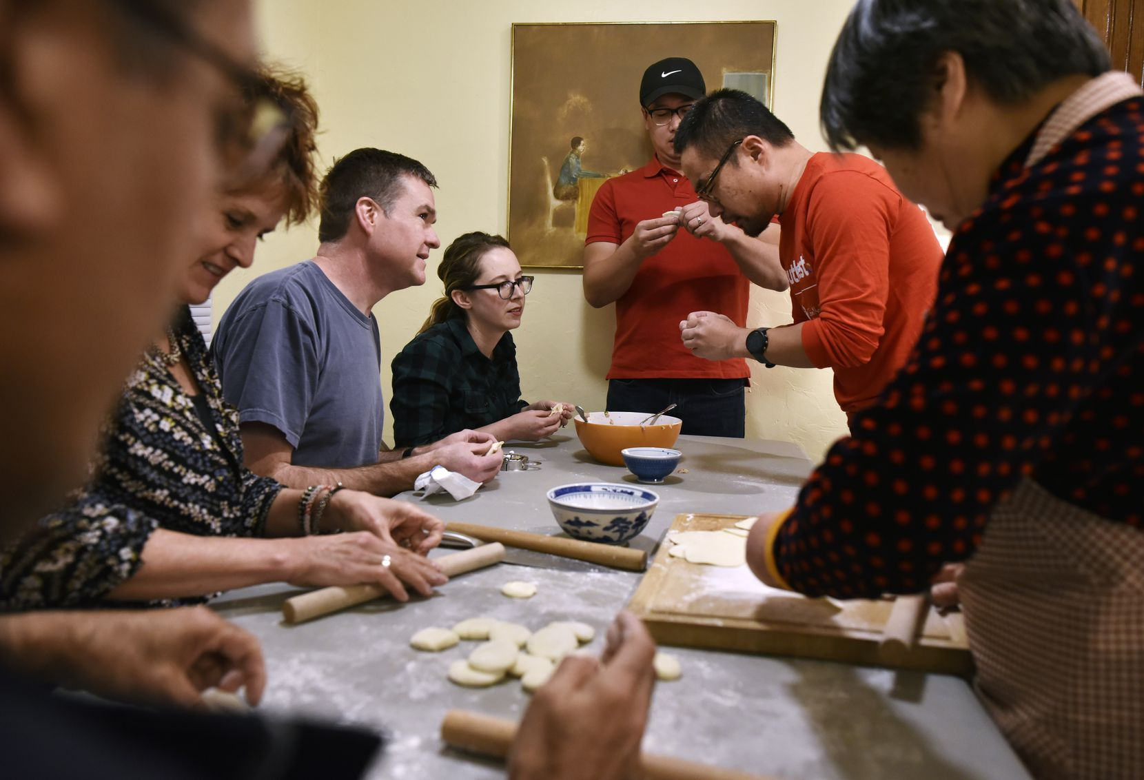 A group of friends and family, led by Lin Wang (top-right) work on forming Chinese dumplings during a Chinese New Years party in Dallas on Saturday, Feb. 2, 2020.