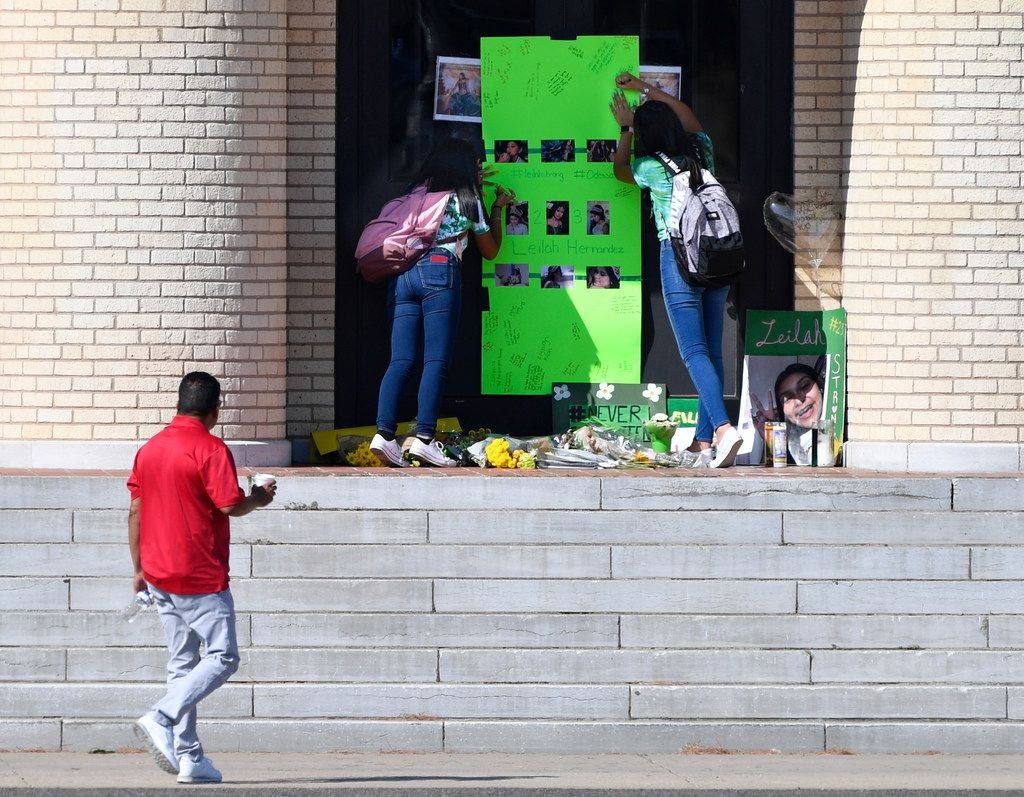 Students write their thoughts on a memorial for Leilah Hernandez on the front steps of Odessa High School on Sept. 3, 2019. The 15-year-old student was the youngest of seven people killed in a shooting rampage on Saturday.