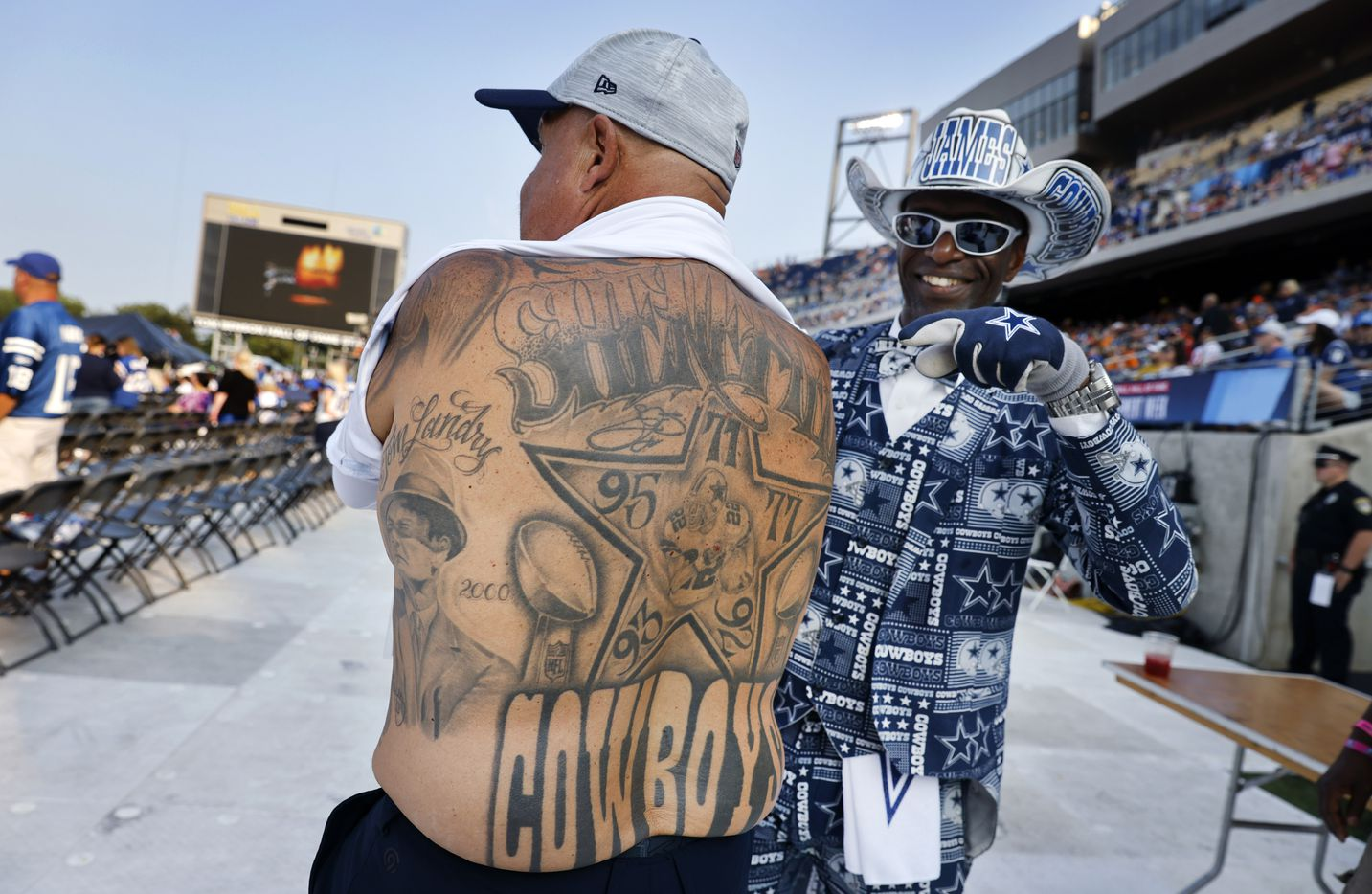 Mark Shenefild shows off his Dallas Cowboys themed tattoos covering his back as pointed out by James Wright of DeSoto before Pro Football Hall of Fame inductee Drew Pearson was introduced during the Class of 2021 enshrinement ceremony at Tom Benson Hall of Fame Stadium in Canton, Ohio, Sunday, August 8, 2021. (Tom Fox/The Dallas Morning News)