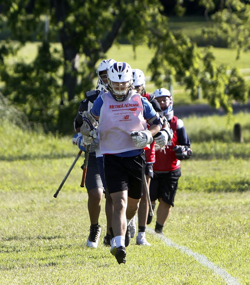 Homero Ortiz leads fellow members of the Bridge Eagles lacrosse team as they run a lap around their practice field to warm-up before drills. The Bridge lacrosse team held their Wednesday evening practice session at the JC Phelps Recreation Center in Dallas on May 5, 2021.