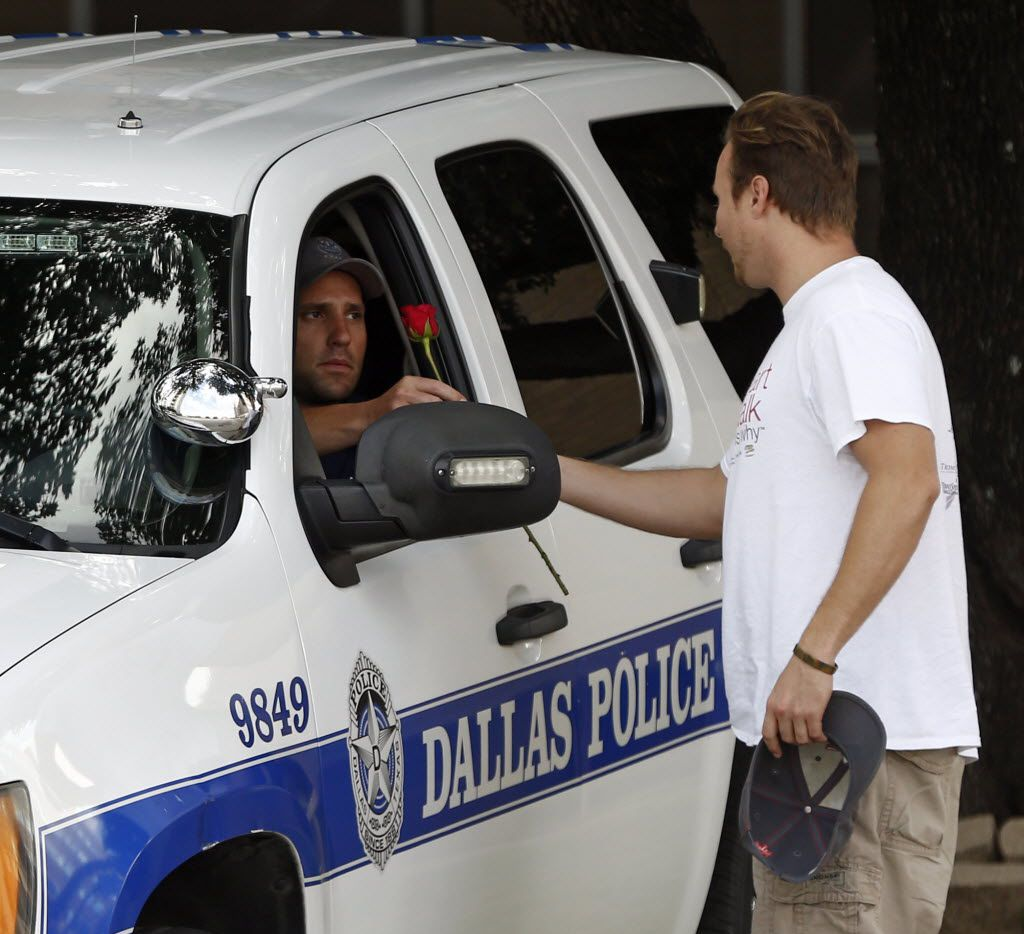 John Fife, minister at One Souls Night, hands a police officer guarding Jack Evans Police Headquarters a rose on July 8, 2016, after a deadly shooting in downtown Dallas.