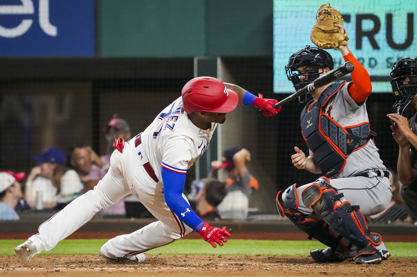 Texas Rangers first baseman Andy Ibanez is spins away from an inside pitch from Detroit Tigers relief pitcher Buck Farmer as catcher Jake Rogers reaches for the pitch during the fifth inning at Globe Life Field on Tuesday, July 6, 2021.