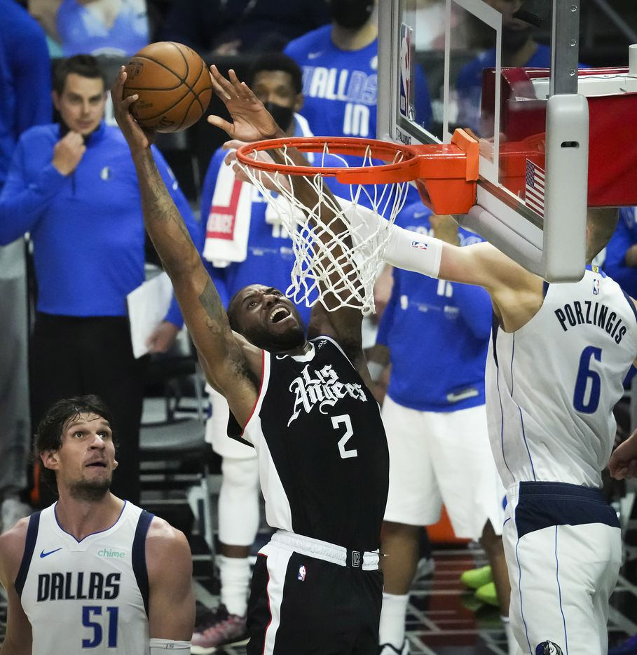 LA Clippers forward Kawhi Leonard (2) dunks the ball past Dallas Mavericks center Kristaps Porzingis (6) and center Boban Marjanovic (51) during the third quarter of Game 7 of an NBA playoff series at the Staples Center on Sunday, June 6, 2021, in Los Angeles.