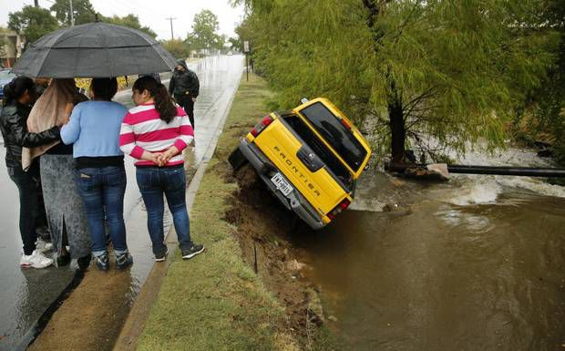 Rosalinda Reyes (centro, bajo el paraguas) es consolada por amistades luego de que su camioneta derrapara y terminara en un arroyo en Arlington.   (TOM FOX/DMN)