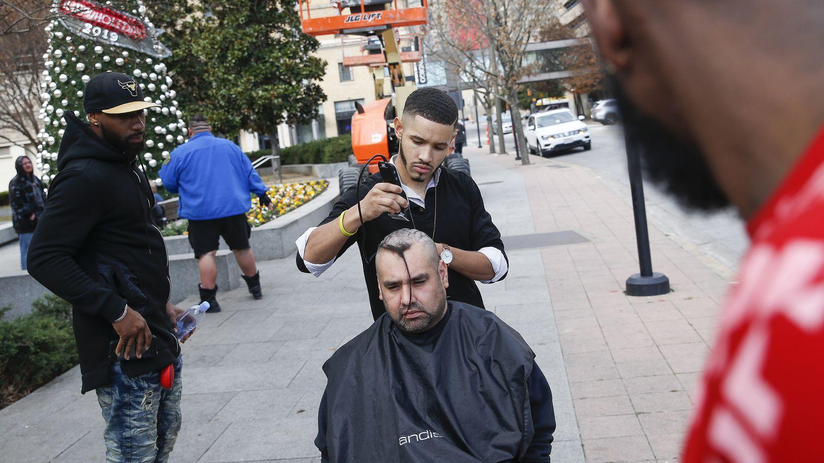 Isiah Knight, de Missouri, corta el cabello a Kevin Briggs de San Francisco, en una banqueta del Main Street Park, en el centro de Dallas.