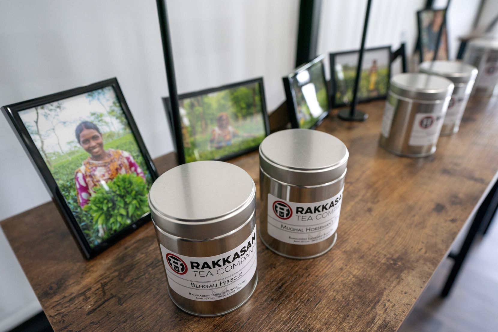 Canisters of Rakkasan Tea sit in front of photos of tea growers from the countries where the tea was sourced.
