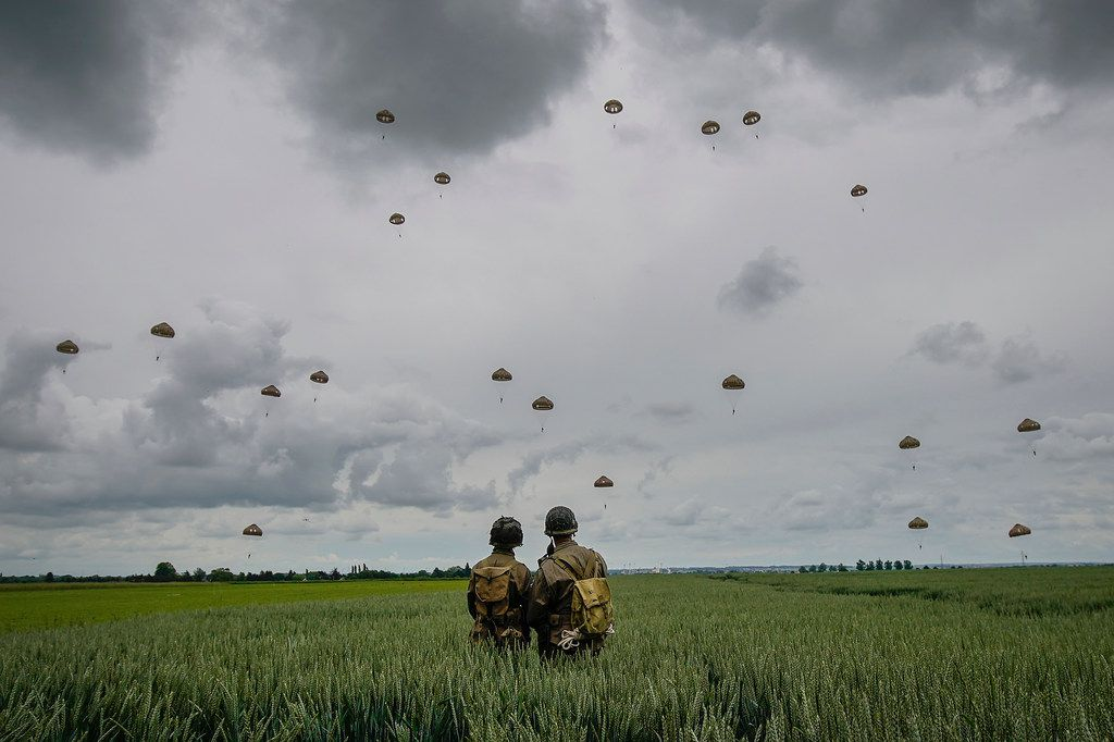 Military re-enactors look on as 280 paratroopers take part in a parachute drop onto fields on June 5, 2019, at Sannerville, France. Veterans, families, visitors and military personnel are gathering in Normandy on June 6 to commemorate the 75th anniversary of the Normandy Landings which heralded the Allied advance toward Germany and victory in Europe 11 months later.