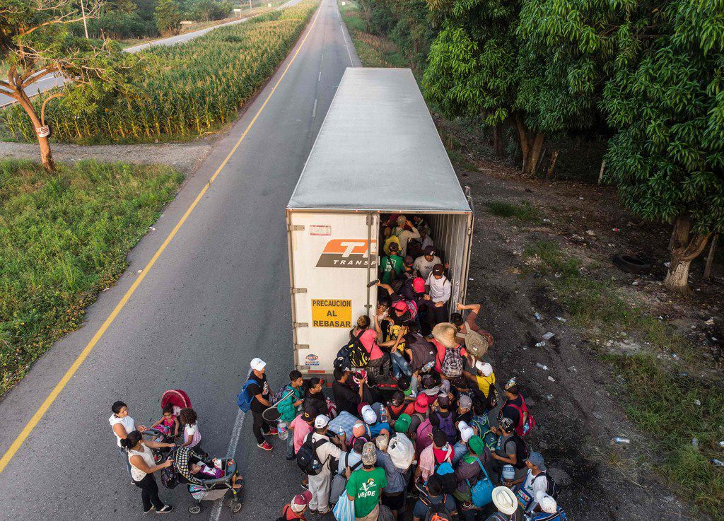 Honduran migrants taking part in a caravan heading to the United States get on a truck, near Pijijiapan, southern Mexico on October 26, 2018.