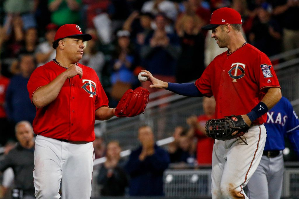 Minnesota Twins starting pitcher Bartolo Colon gets the game ball from first baseman Joe Mauer after the Twins defeated the Texas Rangers 8-4 in a baseball game Friday, Aug. 4, 2017, in Minneapolis. (AP Photo/Bruce Kluckhohn)