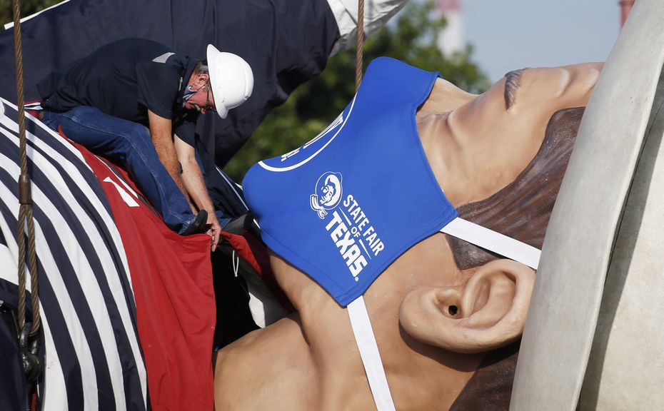 Up, up and away: Tim Thibodeaux works on the collar of Big Tex as he is prepared for installation at Fair Park in Dallas on Wednesday, Sept. 16, 2020.