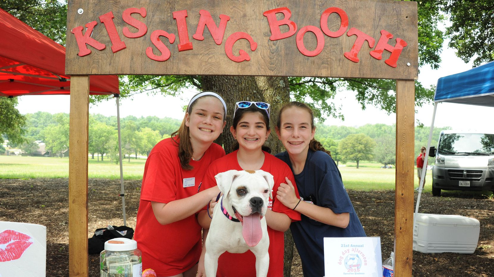 Volunteers Evan Johnston, Claudia Held and Kathleen Roberts helped Sugar Pie get adopted at the kissing booth at the 21st annual Dog Day Afternoon.