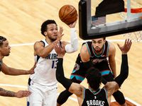 Dallas Mavericks guard Jalen Brunson (13) shoots from between Memphis Grizzlies forward Dillon Brooks (24) and Brandon Clarke, left, during the second half of an NBA basketball game Tuesday, May 11, 2021, in Memphis, Tenn.