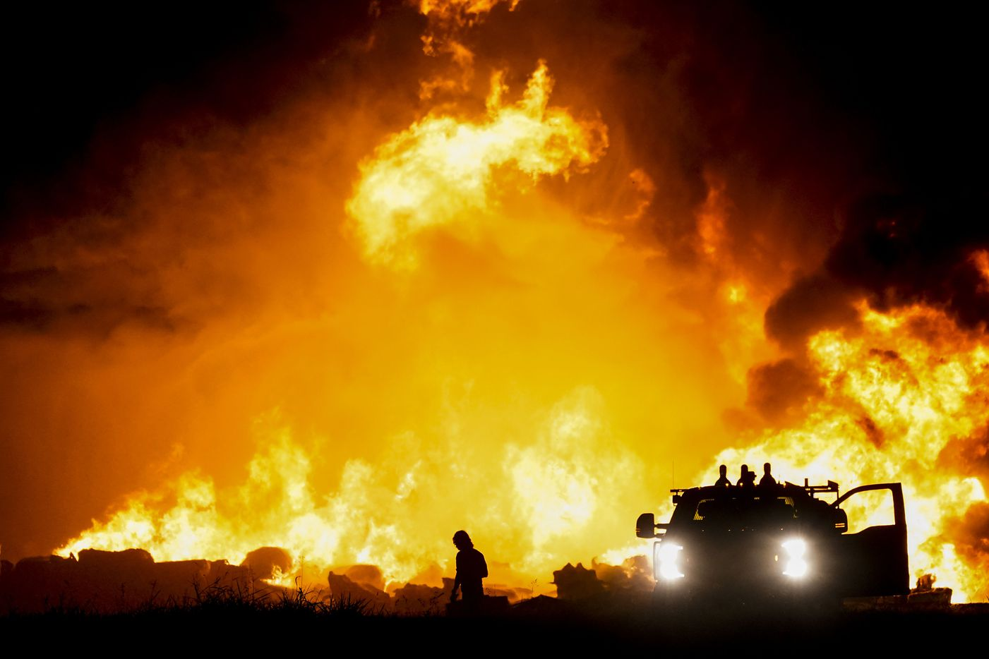 Fire crews battle a massive blaze in an industrial area of Grand Prairie, Texas, in the early morning hours of Wednesday, Aug. 19, 2020. The fire is in the 2000 block of West Marshall Drive, near the Bush Turnpike. Among the businesses in the area is Poly-America, a company that produces trash bags and other plastic products. (Smiley N. Pool/The Dallas Morning News)