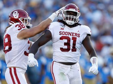 LOS ANGELES, CALIFORNIA - SEPTEMBER 14:  Bryan Mead #38 congratulates Jalen Redmond #31 of the Oklahoma Sooners after his sack of Dorian Thompson-Robinson #1 of the UCLA Bruins during the first half of a game on at the Rose Bowl on September 14, 2019 in Los Angeles, California. (Photo by Sean M. Haffey/Getty Images)