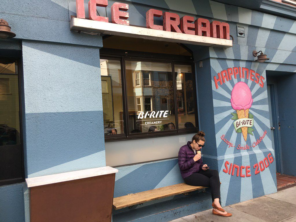 A customer enjoys her ice cream at Bi-Rite Creamery on 18th Street in San Francisco's Mission area.