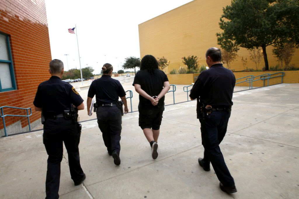 """A 15-year-old student is taken from a Dallas high school to a Dallas County Truancy Court after being served a """"Directive to Apprehend"""" by Precinct 5 Deputy Constable and Truancy Officer Carolina Garcia (second from left) and Precinct 5 Deputy Constable Randy Mitchell (far right) on Friday, September 16, 2011.  DISD Police Officer Pat Gross is on the far left. (Lara Solt/The Dallas Morning News) / cuffs - handcuffs - cuffed - handcuffed / 10012011xALDIA 06192013xNEWS 10242014xNEWS"""