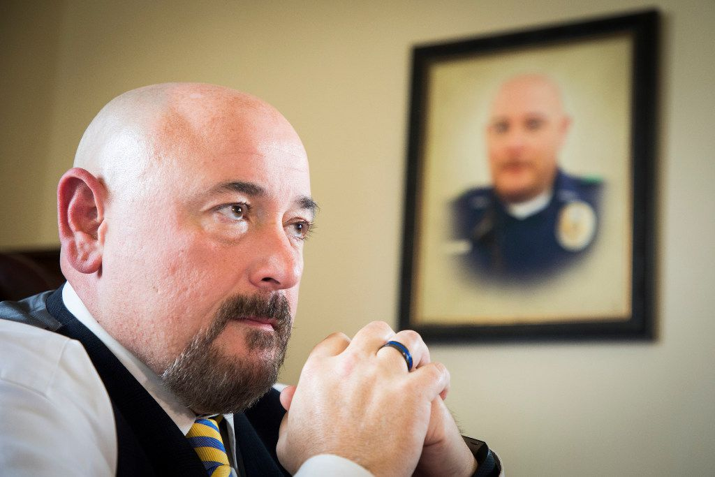 A photograph of Brent Thompson hangs on the wall next to the desk of his brother, Navarro County District Attorney Lowell Thompson. He wears a black and blue ring each day in memory of his brother. He says he's found some comfort in the ways his brother continues to touch lives, such as through scholarships for police academy students and a fund for families of fallen officers.
