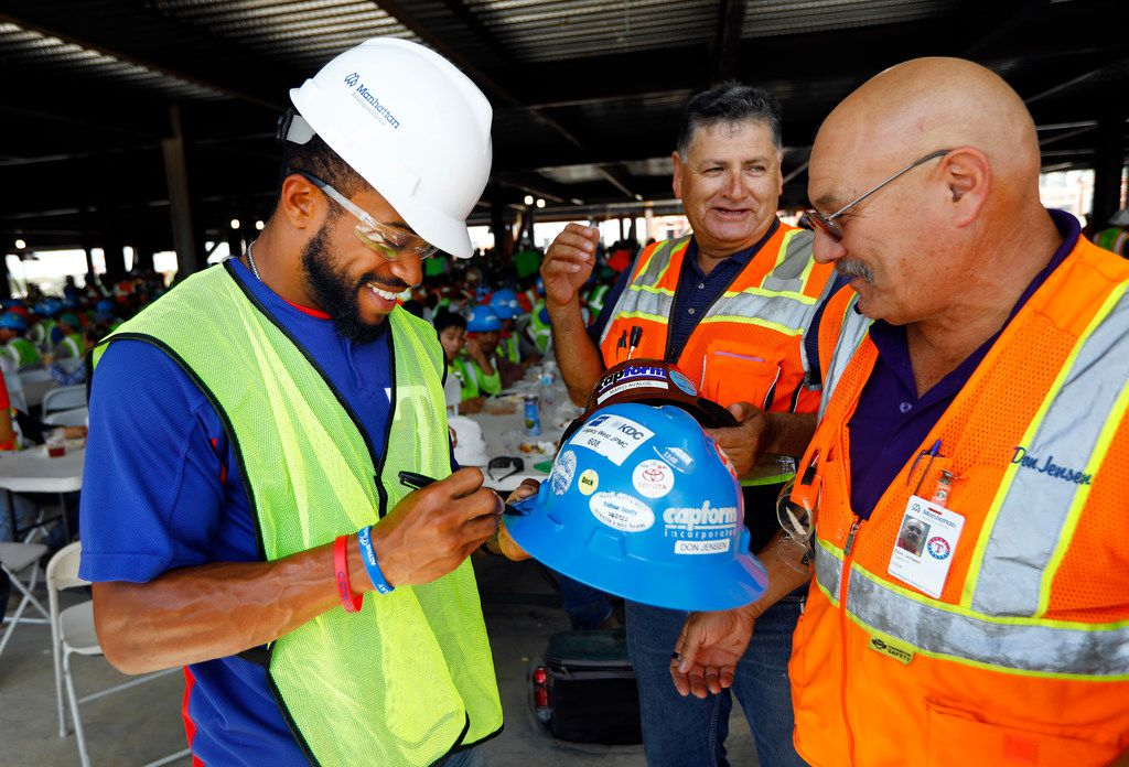 Texas Rangers outfielder Delino DeShields (left) signed construction worker Don Jensen's helmet at the new Globe Life Field under construction in Arlington, Texas, Tuesday, September 18, 2018. The Texas Rangers celebrated the One Million Man Hours by providing a barbecue lunch for it's nearly 900 construction workers. Rangers baseball players joined manager Jeff Banister in handing out construction helmet stickers to mark the occasion. They also signed autographs and posed for photos.